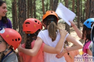 Two campers wearing rock climbing helmets face away from the camera with their arms around each other.