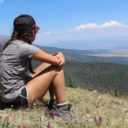 A girl sits on a hill with a view. Her back is towards the camera.